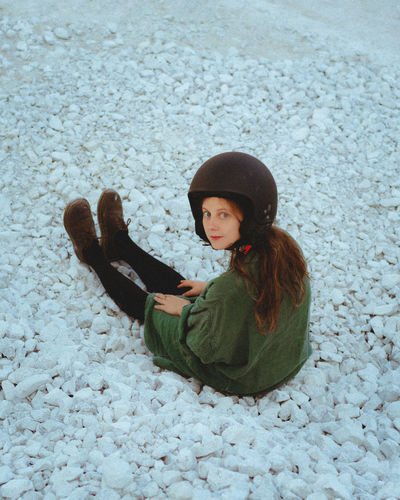 High angle view of woman sitting on snow
