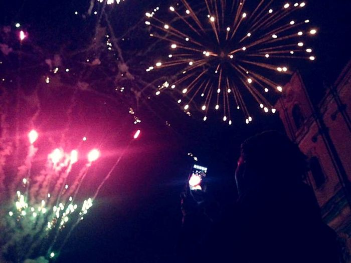 People photographing firework display at night