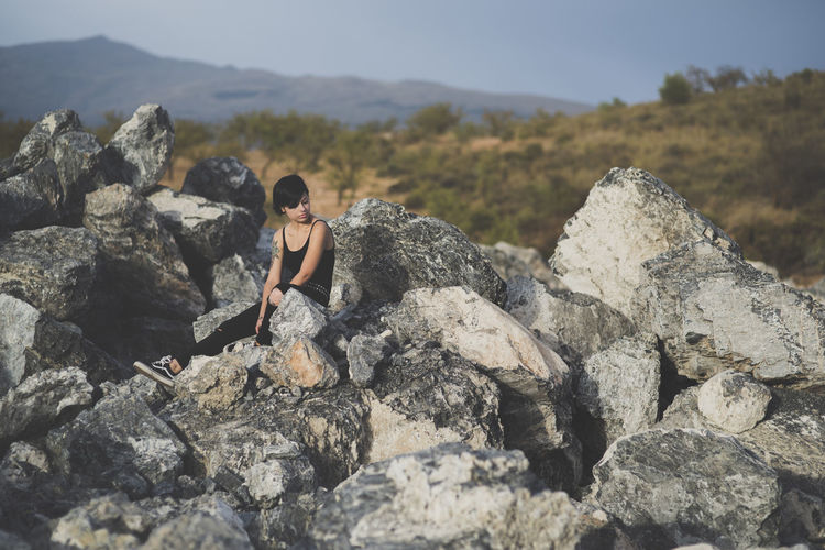 Beautiful young woman wearing black clothes and short haircut sitting on the rocks brunette girl thinking relaxed with closed eyes in the countryside. Beauty In Nature Day Full Length Leisure Activity Lifestyles Mountain Nature One Person Outdoors Real People Rock Rock - Object Rock Formation Sitting Solid Sunlight Women Young Adult Young Women