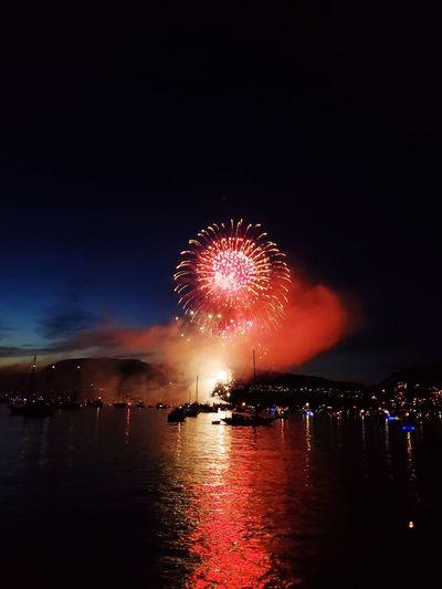 Firework display over illuminated city against sky at night