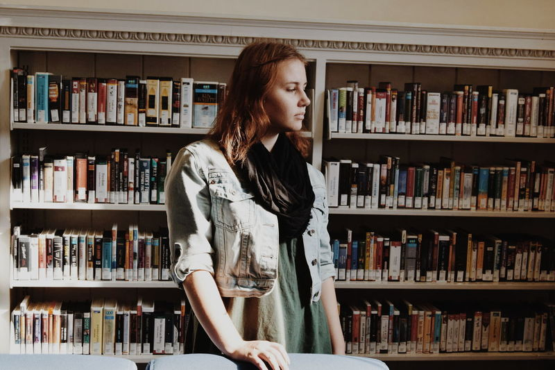 Young woman standing against bookshelf in library