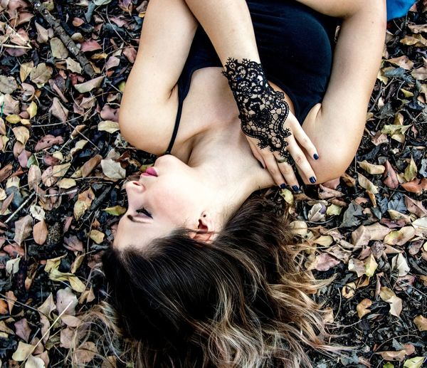 High angle view of beautiful young woman lying on field with dried leaves