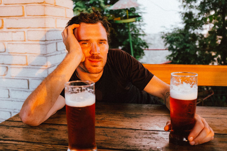 Portrait of man having beer at table during sunset