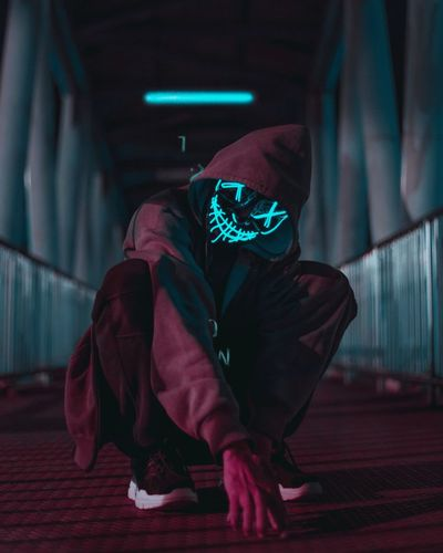 Young man in mask crouching under tunnel at night