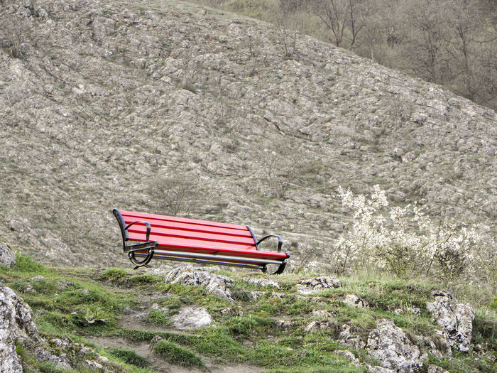Empty bench on rock against mountain