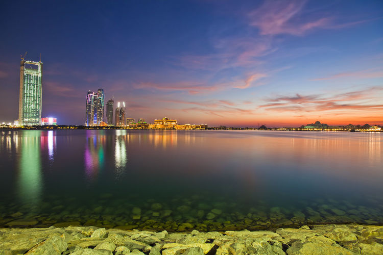 Abu Dhabi skyline at sunset Abu Dhabi UAE Abudhabi Architecture Beauty In Nature Building Building Exterior Built Structure City Cloud - Sky Illuminated Modern Nature No People Office Building Exterior Outdoors Reflection Scenics - Nature Sky Skyscraper Sunrise Uae,abudhabi Urban Skyline Water Waterfront