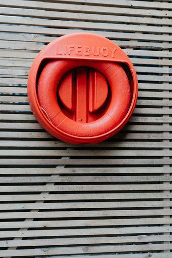 A lifebuoy hung on a wooden lattice wall Lattice Architecture Circle Close-up Communication Day Lifebuoy No People Outdoors Pattern Red Road Sign Safety Textured  Wooden Background