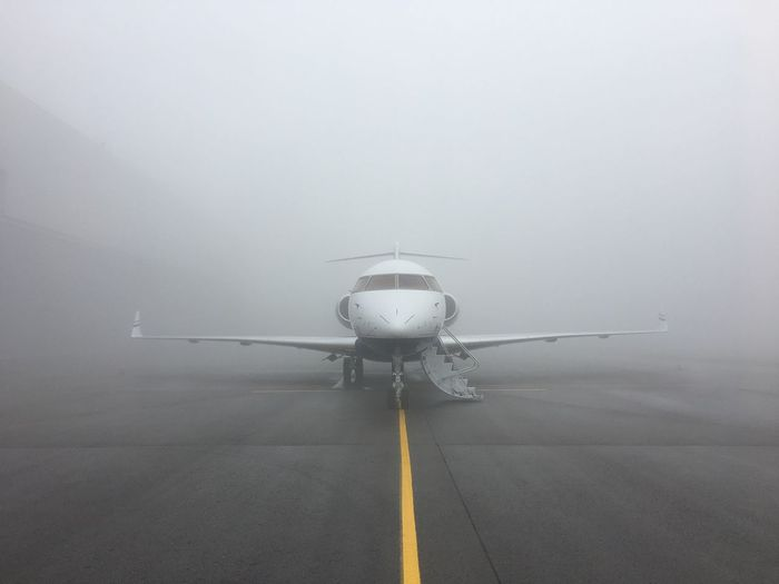 Airplane Transportation Air Vehicle Airport Airport Runway Runway No People Day Nature Outdoors Passenger Boarding Bridge Fog