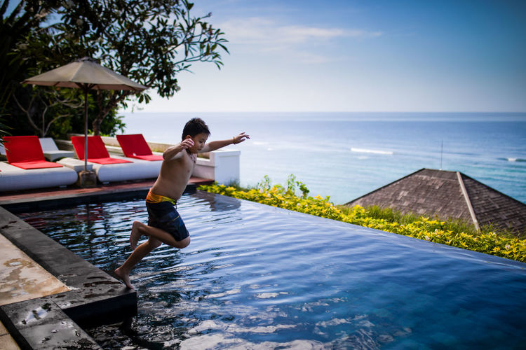Full length of shirtless boy jumping in infinity pool at resort