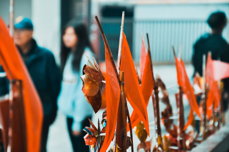 Close-up of orange decoration with people in background