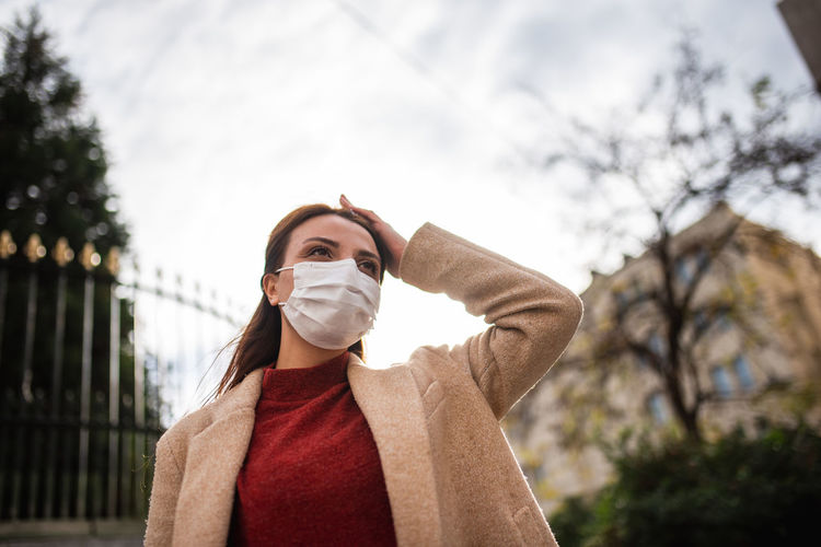 Low angle view of woman wearing mask standing against sky