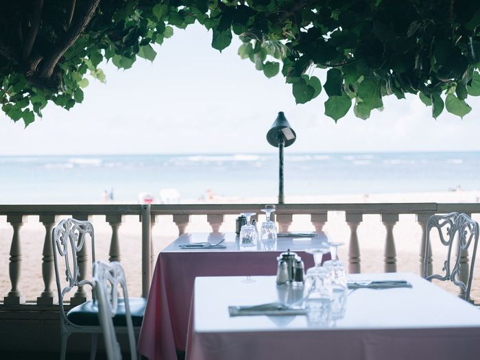 Empty Chairs And Tables At Restaurant By Sea