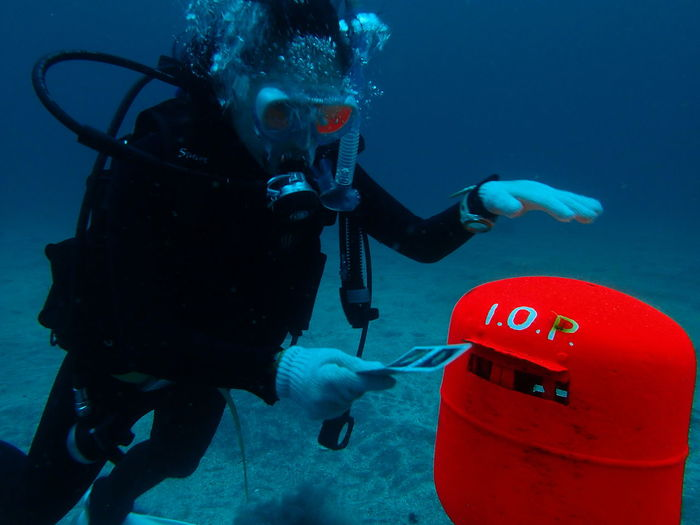 Underwater View Of Scuba Diver Posting Letter In Mailbox