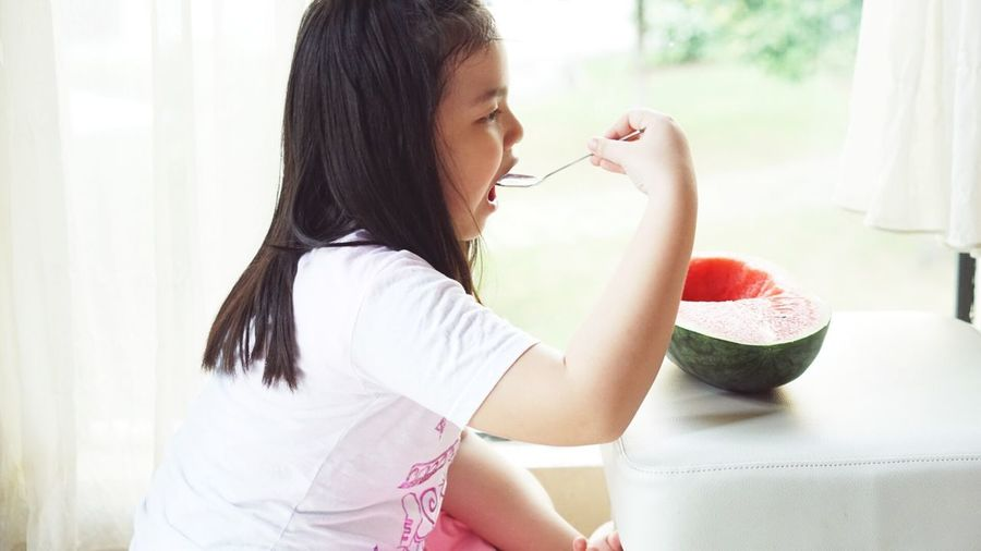 Side View Of Smiling Girl Having Watermelon At Home