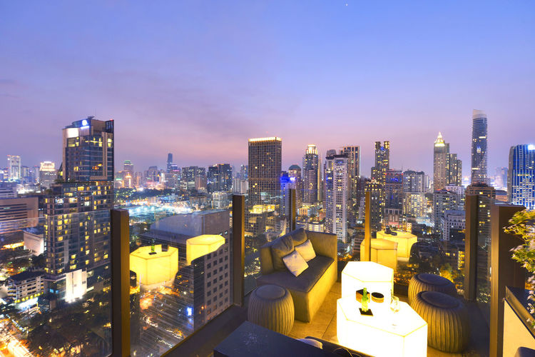 Bangkok city view point from rooftop bar, overlooking a magnificent cityscape blue sky and city light, Thailand Bangkok Building Business Couch Dinner Exterior Food And Drink Terrace Travel Twilight Bar Drink Evening Landscape Night Outdoor Relaxation Restaurant Rooftop View  Urban