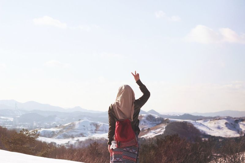 Rear view of woman standing on mountain peak with peace sign