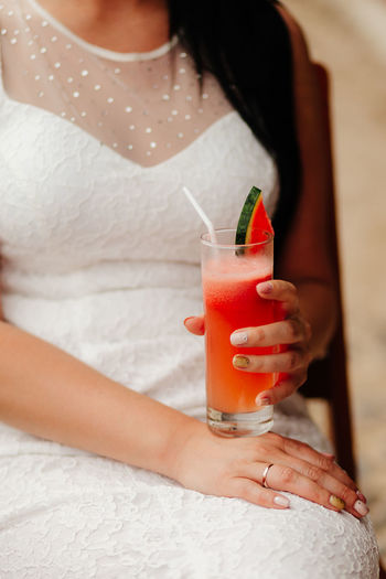 Midsection of woman holding drink