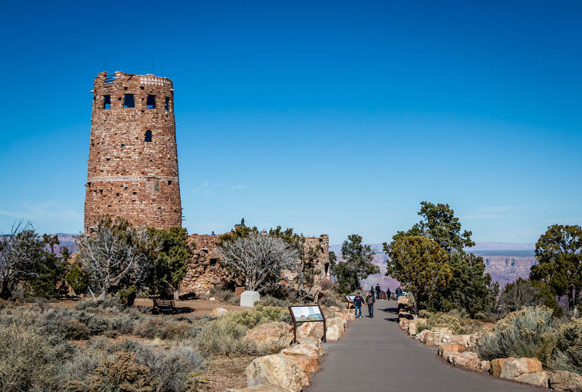 Desert View Tower at Grand Canyon Arizona Brick Wall Desert View Tower Grand Canyon Architecture Blue Building Building Exterior Built Structure Clear Sky Day History Outdoors Plant Sky Sunlight The Past Tower Tree