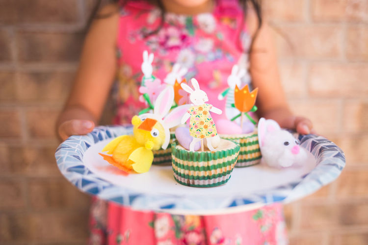 Midsection of girl holding plate with multi colored easter bunnies