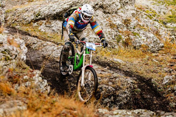 Full length of man riding mountain bike on rocks
