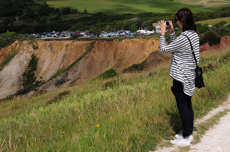 Full Length Side View Of Woman Photographing While Standing On Cliff