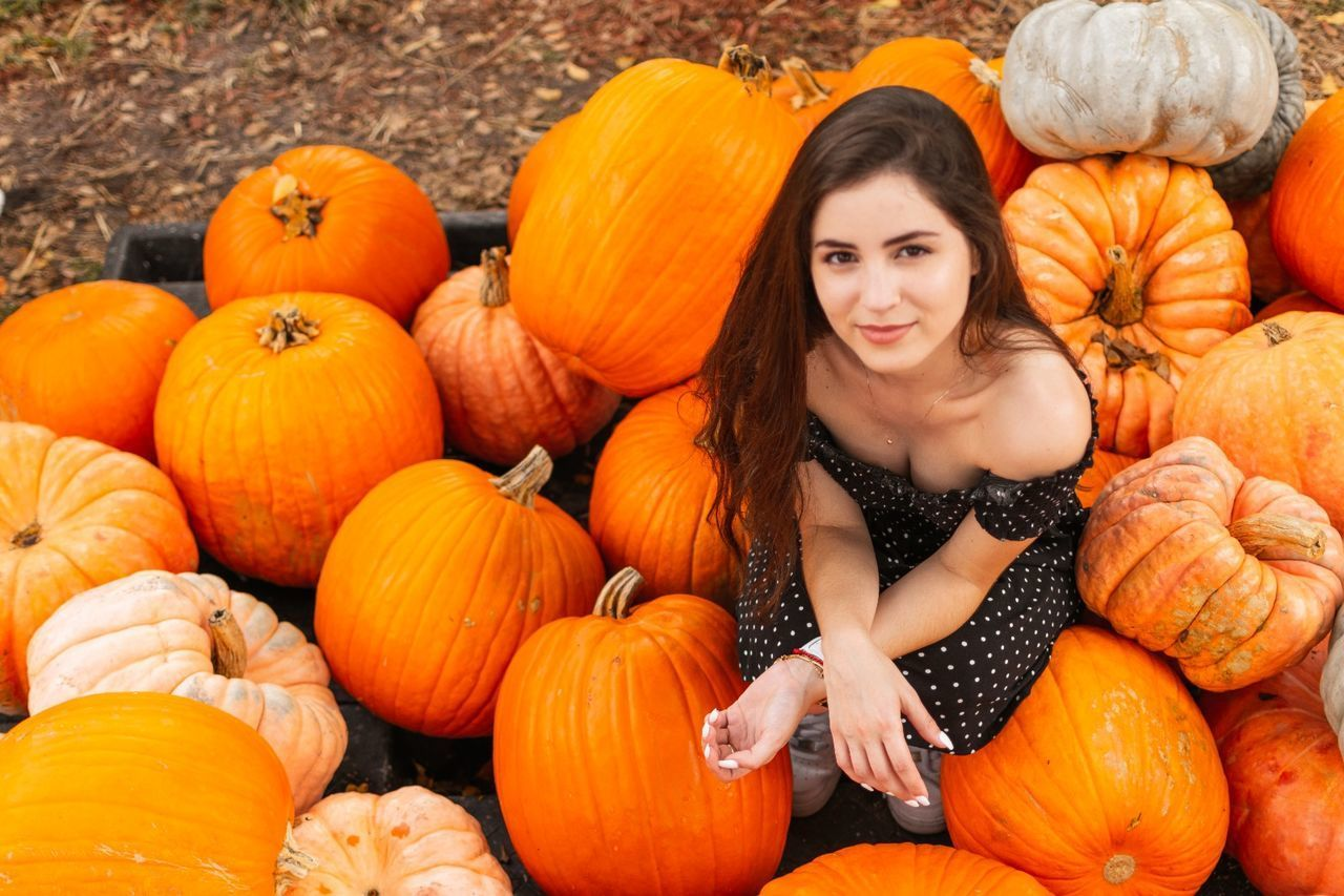 PORTRAIT OF A SMILING YOUNG WOMAN WITH ORANGE PUMPKINS