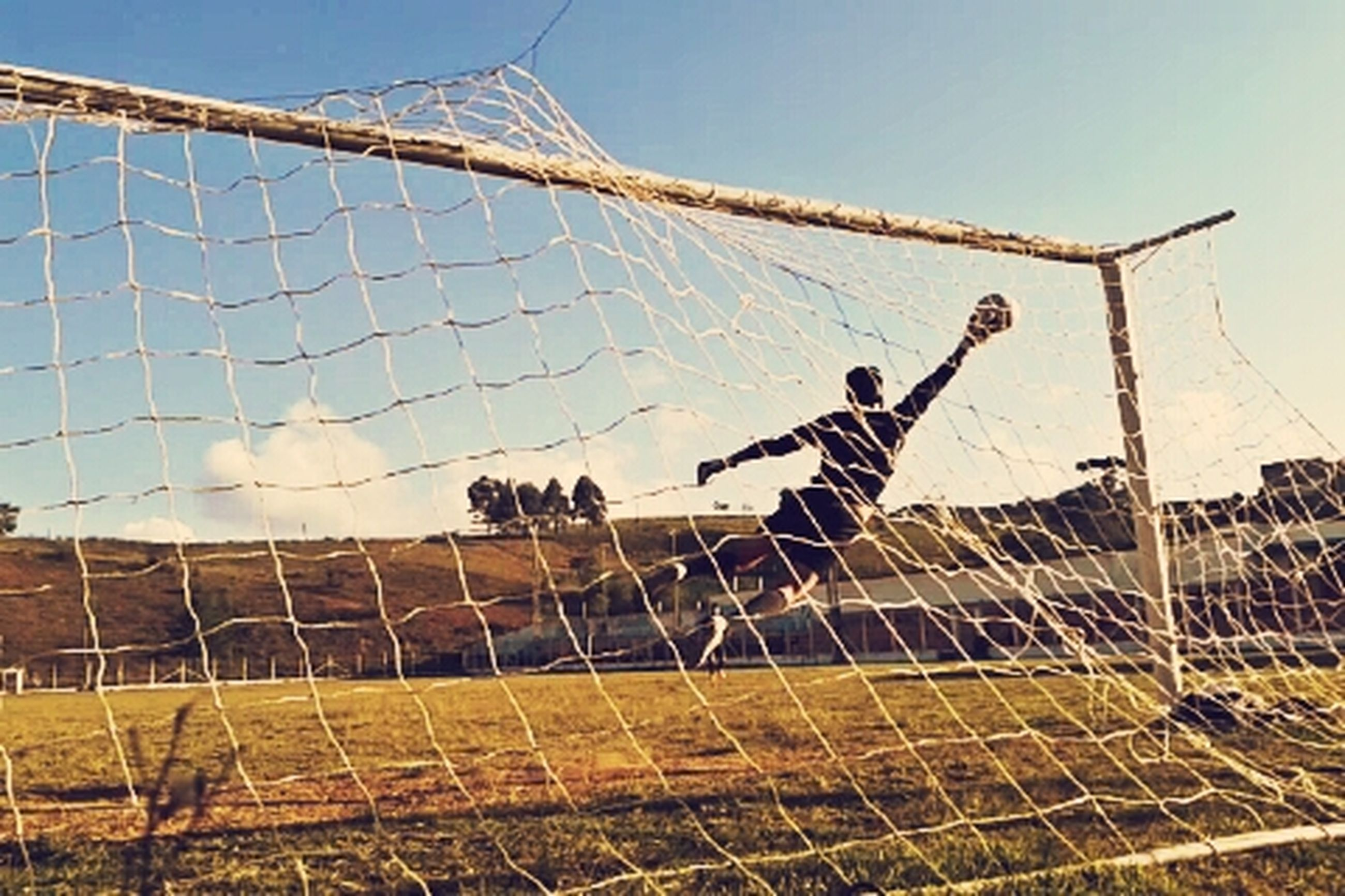 fence, field, sport, leisure activity, lifestyles, men, sky, chainlink fence, grass, day, protection, built structure, building exterior, clear sky, safety, full length, architecture, outdoors