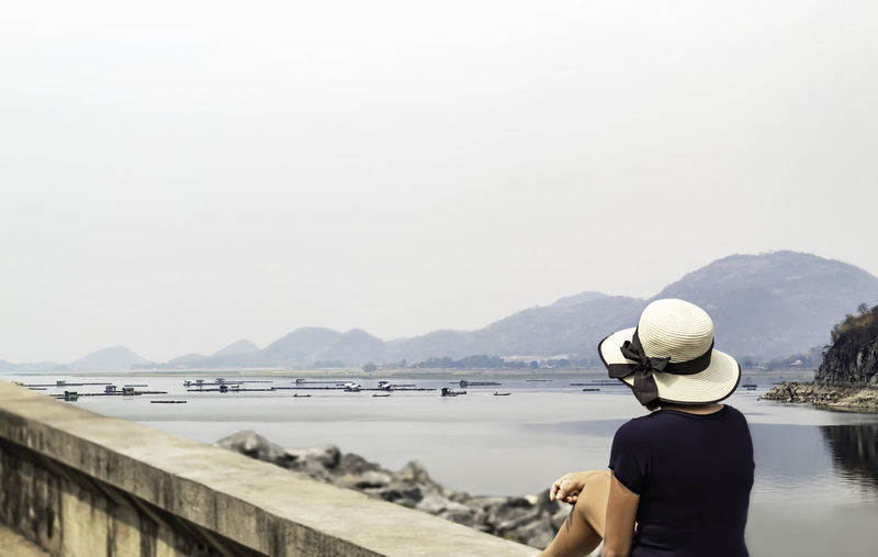Rear view of woman looking at view sitting on retaining wall