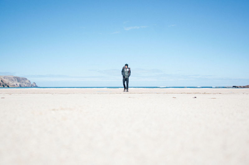 Full length of man standing at beach against sky