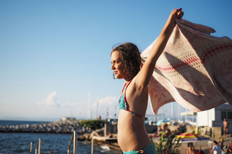 Side view of girl holding towel at beach