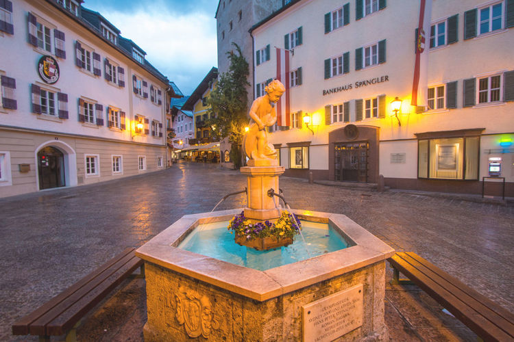 Town Square fountain in Zell Am See town in Austria in the evening Austria Fountain Light Tourist Architecture Dusk Europe Illuminated Outdoors Sculpture Statue Street Tourism Travel Destinations Zell Am See