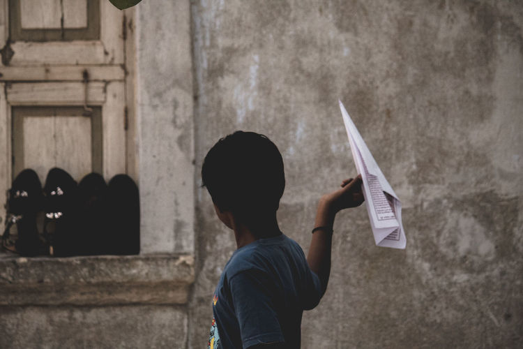 Boy holding paper airplane by old house