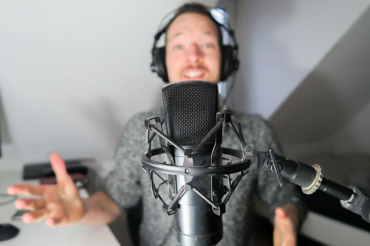 Young male podcaster, youtuber with condenser microphone Communication Technology One Person Microphone Listening Portrait Music Input Device Indoors  Headphones Front View Adult Talking Headshot Holding Human Body Part Arts Culture And Entertainment Women