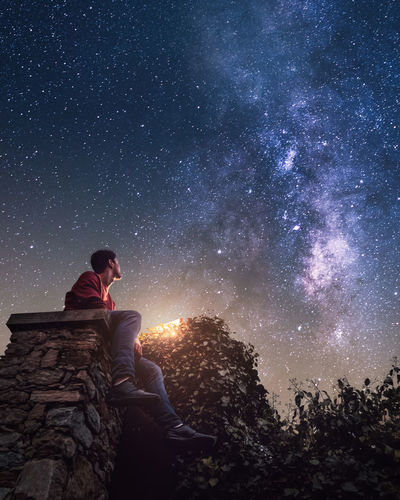 Low angle view of man sitting against sky at night