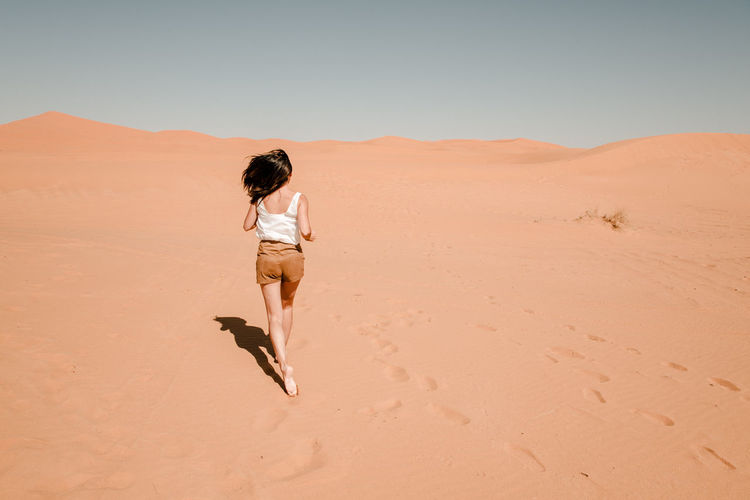 Young woman running through the sand dunes in the desert of the sahara