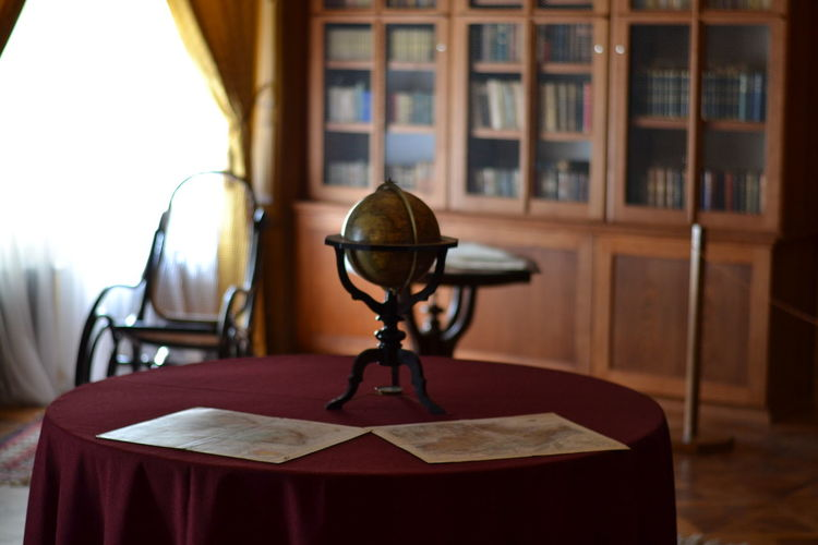 Globe on table against shelf in library