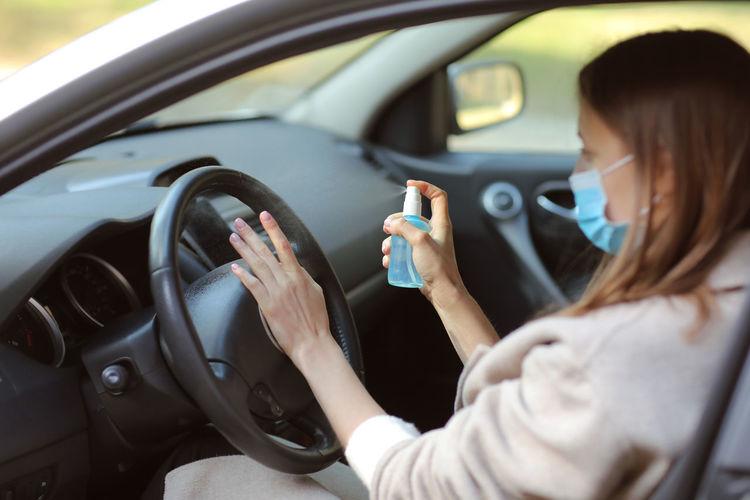 Woman spraying sanitizer on steering wheel