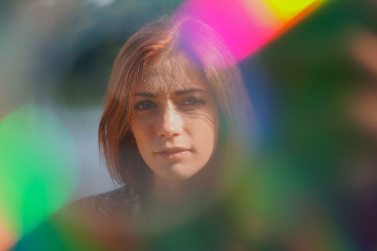 Funky colorful portrait of a young woman with lens flare and light leaks