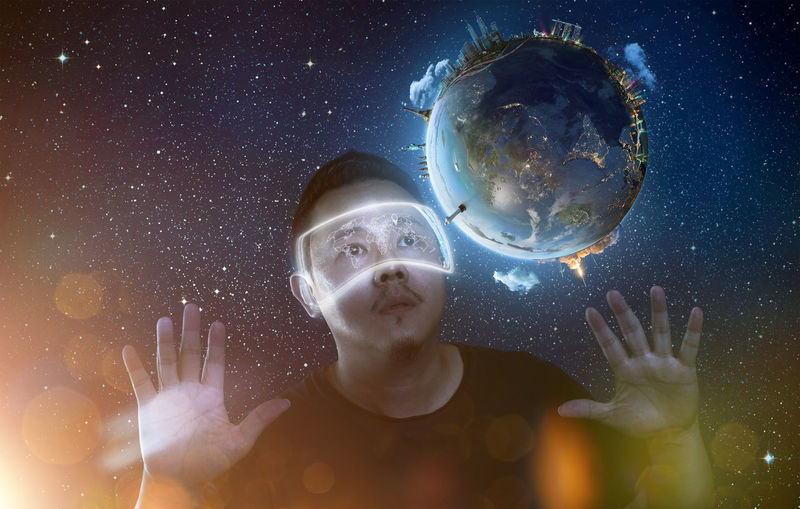 Digital composite image of man wearing eyewear looking at planet earth