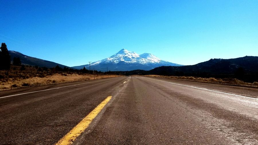 View of highway leading towards snowcapped mountain
