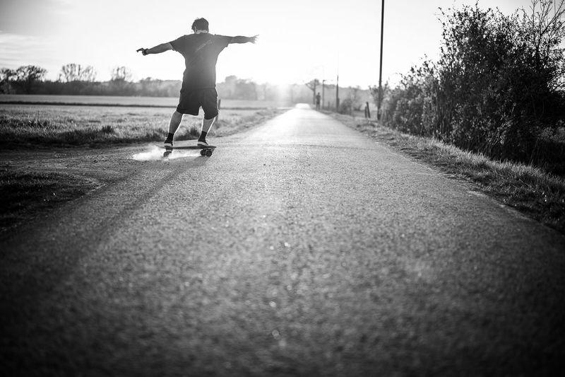 Rear view of man skateboarding on road against sky