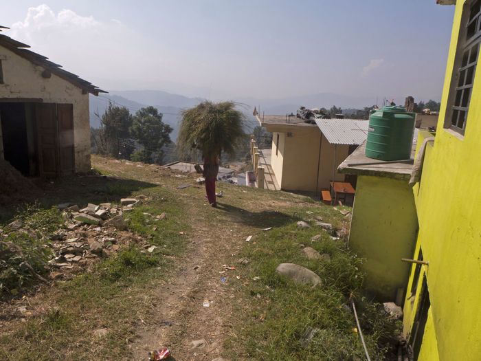 A woman carries hay on her head and is on her way home from the field Carrying Footpath Hay Bale Himalayas India Rural Travel Trekking Woman Working Working Woman Built Structure Countryside Hay Hiking Trail House Mountain Mountain Range Pathway Town Uttarakhand Village