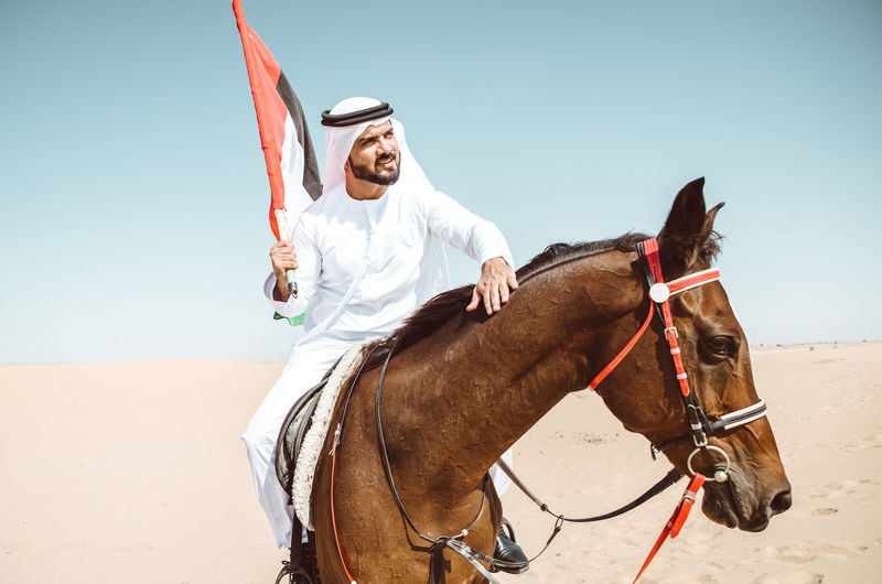 Man With Horse Standing In Desert