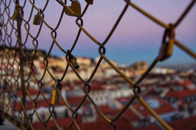 Close-up of padlocks on chainlink fence against sky