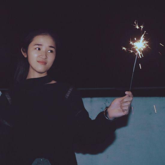 Portrait of boy holding sparkler at night