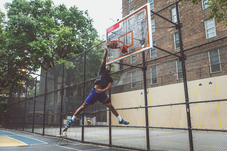 Young man scoring goal at basketball court