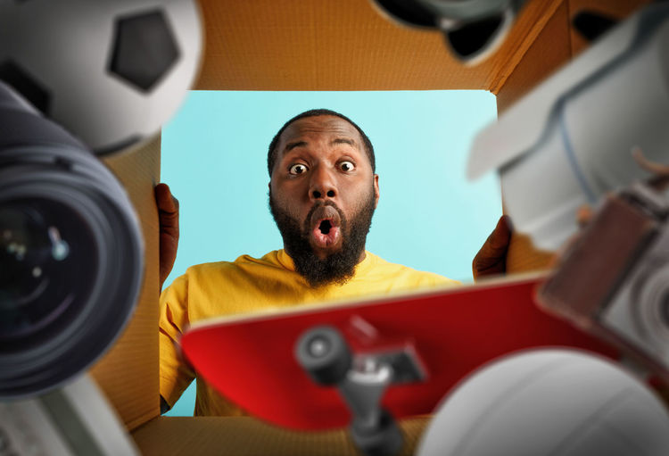Low angle portrait of shocked man peeking in box