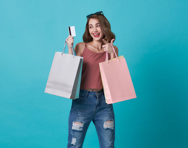 Happy woman holding shopping bags while standing against turquoise background