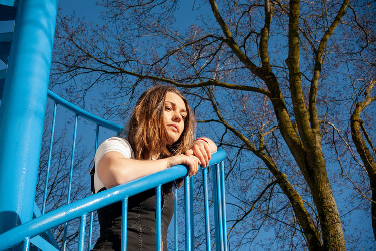 Full length of young woman on bare tree against blue sky