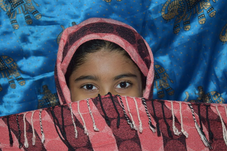 Close-up portrait of girl covering face with scarf at home